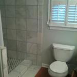 White Grecian marble shower, new toilet, flooring, and trim
