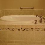 Custom-designed space for drop-in jacuzzi tub with mosaic tile detailing